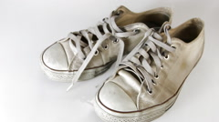 Old sneakers on white background Stock Footage