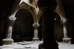Stock Photo of Interior of medieval christian temple Geghard with columns, and ancient inscr