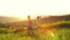 Active Couple Trail Running Outside On Mountain At Sunset - stock footage