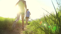 Low Angle  Couple Running Outside At Sunset With Lens Flare Stock Footage