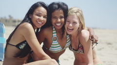 Huddled group of multi ethinic friends men and women having fun at the beach Stock Footage