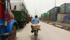 Fresh fruits seller ride bike through dusty old port road, follow shot Stock Footage