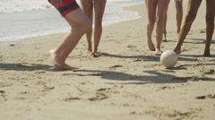 Authentic young group of multi ethnic friends kicking ball on the beach shore - stock footage