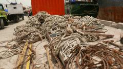 Heap of ropes, wire ropes, hawser and cable on the dusty ground, close up Stock Footage