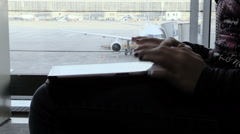 Woman using the tablet computer in the airport with airplain in background Stock Footage