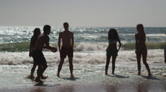 Silhouette group of interracial friends playing volleyball on the beach Stock Footage
