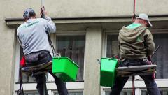 Skilled workers  working  cleaning the window of a building hanging in the air Stock Footage