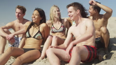 Young adult group of interracial friends sitting talking on the beach Stock Footage