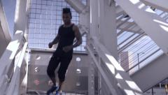 Male Athlete Runs Down Outside Staircase In Urban Setting (4K) Stock Footage