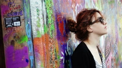 Confused woman stands still with the blank stare against a wall Stock Footage