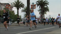 RUNNERS IN SAN FRANCISCO PASS PALM TREES - 211 Stock Footage