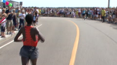 RUNNING RACE LEADER PAST HUGH CROWDS AND UNDER AMERICAN FLAG TO FINISH - 225 Stock Footage