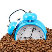 Blue alarm clock buried in beans Stock Photos