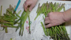 Old woman cutting and peeling asparagus Stock Footage