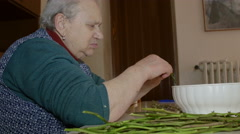 Very old woman cooking wild asparagus Stock Footage