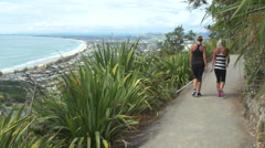 Two friends taking a morning walk on The Mount, Mount Maunganui, New Zealand Stock Footage