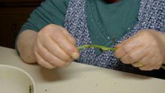 Old woman cooking vegetables: elderly woman peeling asparagus Stock Footage