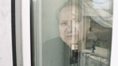 Very old woman at the window: elderly woman beyond the windowpane Stock Footage