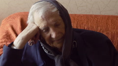 Sad old woman sitting on the sofa Stock Footage