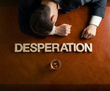 Word Desperation and devastated man composition Stock Photos
