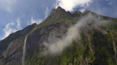 View of Stirling Falls flowing from mountain top at Milford Sound, South Island, Stock Footage