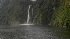 View of Stirling Falls flowing through mountains at Milford Sound, South Island, Stock Footage