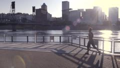 Athlete Runs Along Riverfront Park, Stops To Stretch, Then Continues Running Stock Footage