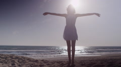 Beautiful woman dancing at the beach in white dress Stock Footage