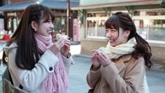Young Japanese women eating a snack in Kawagoe, Saitama Prefecture, Japan Stock Footage
