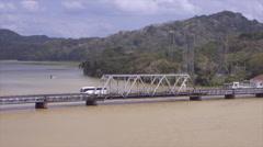 Vehicles moving through one way truss bridge between Gatun Lake and Panama Stock Footage