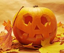 Pumpkin Jack-o'-lantern over maple-leaf - stock photo