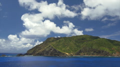 View of Pacific Ocean and mountain covered with greenery in Pitcairn Islands Stock Footage