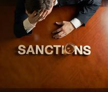 Word Sanctions and devastated man composition Stock Photos