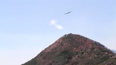 View of airplane extinguishing forest fire over mountains, Camarillo, Stock Footage
