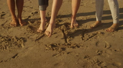 Group of friends using their feet to write on the beach Stock Footage