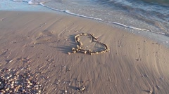 Drawn heart on the sand washed waves Stock Footage
