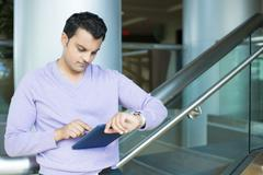Closeup portrait, serious young man in purple sweater checking syncing blue s - stock photo