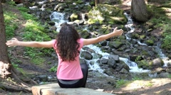 Girl enjoy hands wide open near mountain forest snow melting stream in spring Stock Footage