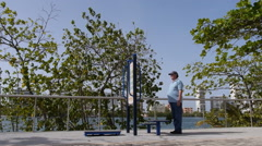 PARK EXERCISE RIG with old senior man Stock Footage