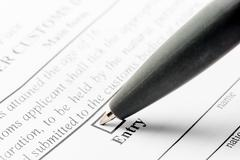 ballpoint pen and declaration form close-up - stock photo