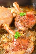 Detail of roast duck legs with caraway and onion - stock photo