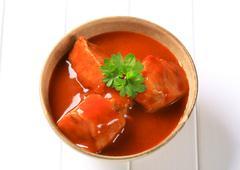 Chunks of pork meat in tomato sauce - stock photo