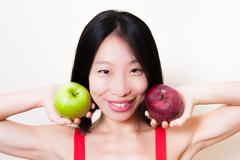 Smiling asian woman close up with green and red apples on white Stock Photos