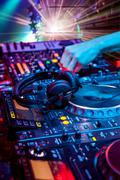 Dj mixes the track in the nightclub at party. In the background laser light s Stock Photos
