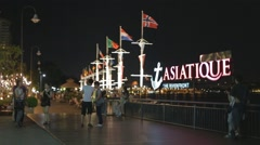 Asian girls pose at Asiatique riverfront sign Stock Footage