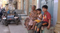 Grandmother and grandchildren sit outside their house - stock footage