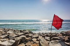 Red flag on rocky beach Stock Photos