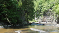 People Wading Above Cane Creek Falls Stock Footage