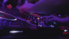Stock Video Footage of Closeup of disk jockey switching buttons on deck, people dancing