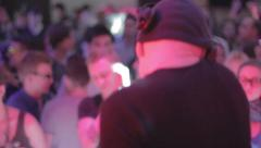 Male disk jockey playing set at nightclub, crowd enjoying music Arkistovideo